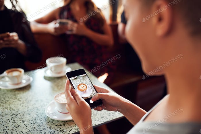 Woman Using Mobile Phone To Take Picture Of Drink In Coffee Shop To Post On Social Media