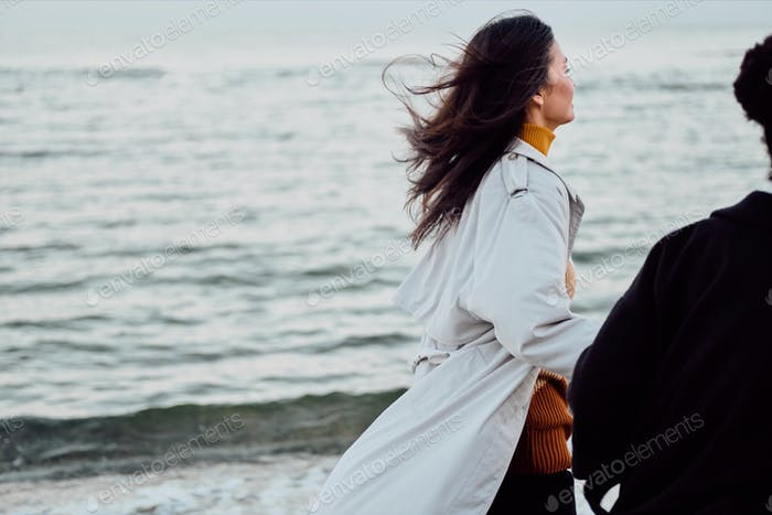 Close up attractive stylish girls in trench coats dreamily walking by the sea
