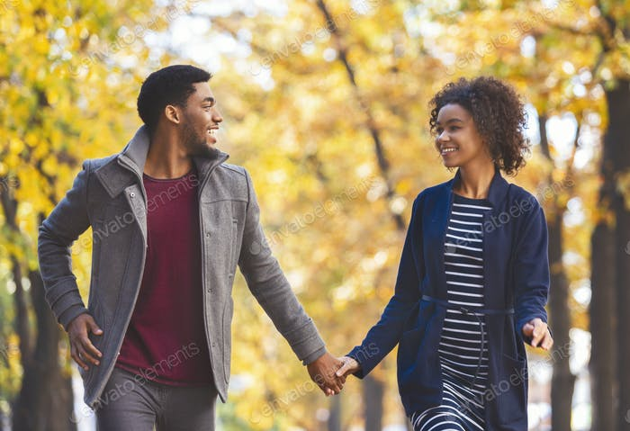 Black couple in holding hands while walking by autumn forest