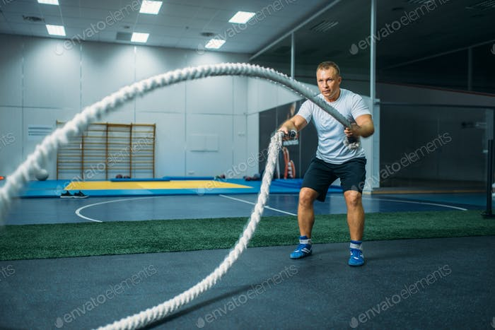 Male athlete with ropes in gym, crossfit workout