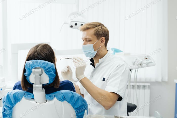 Dentist check patient cavity using instruments at clinic