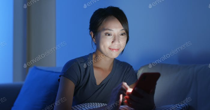 Woman use of smart phone online and sit on the sofa at home