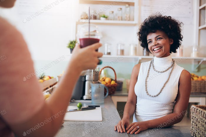 Juice bar owner with customer holding a glass of juice