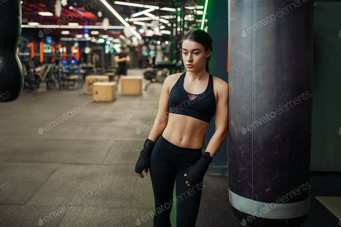 Woman in boxing bandages poses at the punching bag