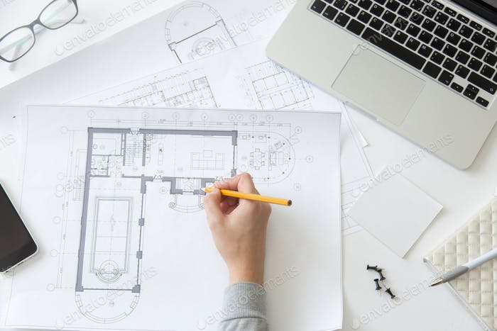 Top view of a hand making an architect drawing