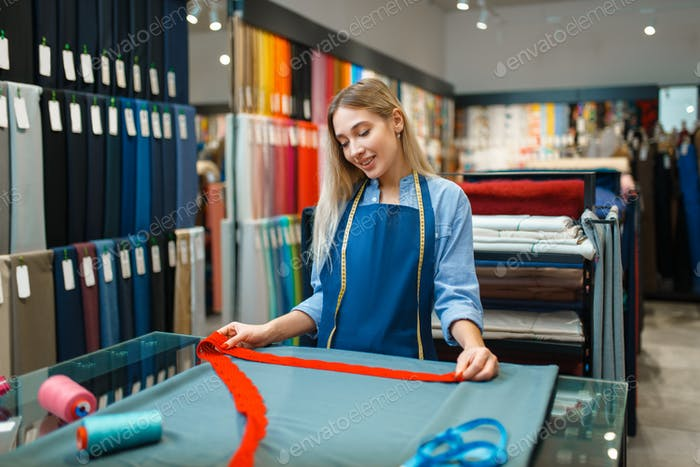 Seamstress measures the fabric in textile store