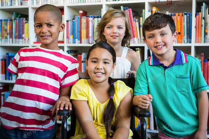 Behinderte Mädchen mit Freunden in der Bibliothek in der Schule