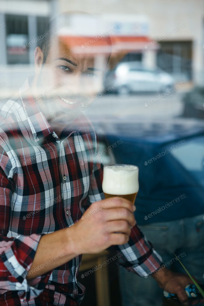 Cheerful man with beer behind the window
