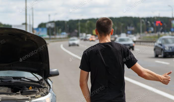 Man hitchhiking and stopping on the road looking for help with his broken car