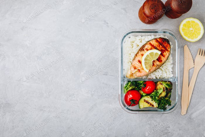 Meal prep containers with salmon and rice and baked vegetables.