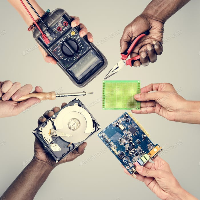 Group of hands holding computer electronics parts on gray background