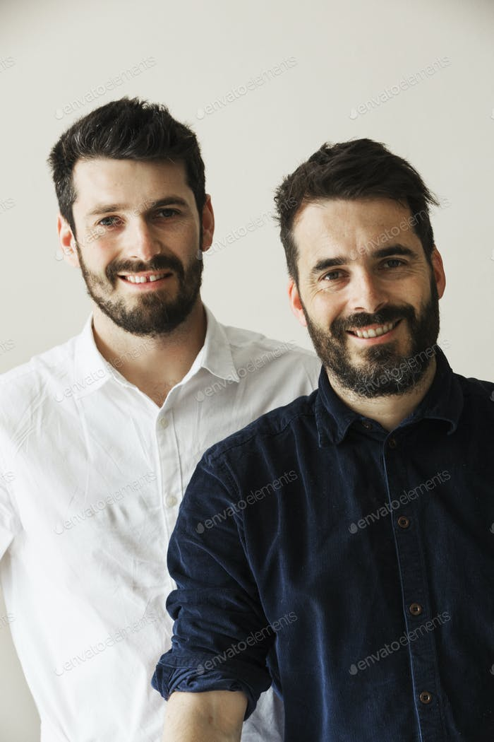 Porträt von zwei bärtigen Männern, die an der Kamera lächeln.