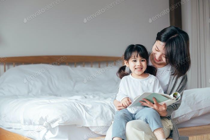 Mutter und Tochter lesen Bücher im Schlafzimmer