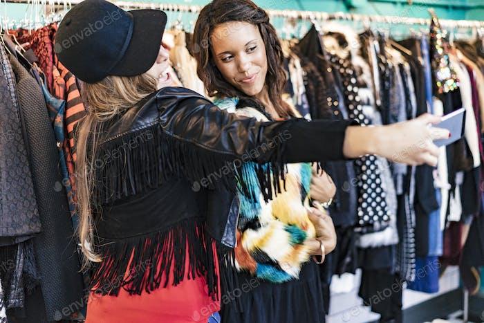 dos amigas de la compra de ropa en una tienda y disfrutar de ella