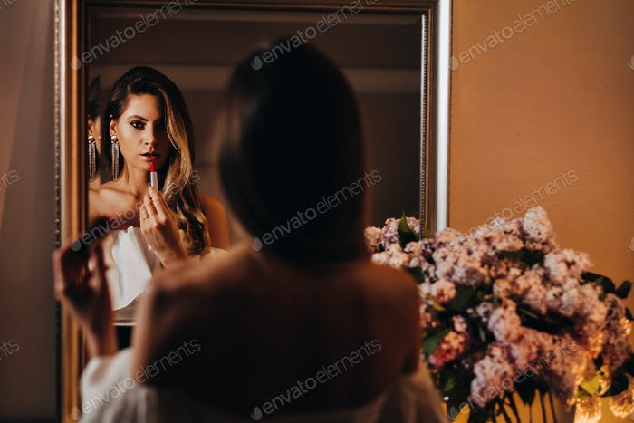A beautiful girl paints her lips in the reflection of the mirror at home. A girl looks in the mirror