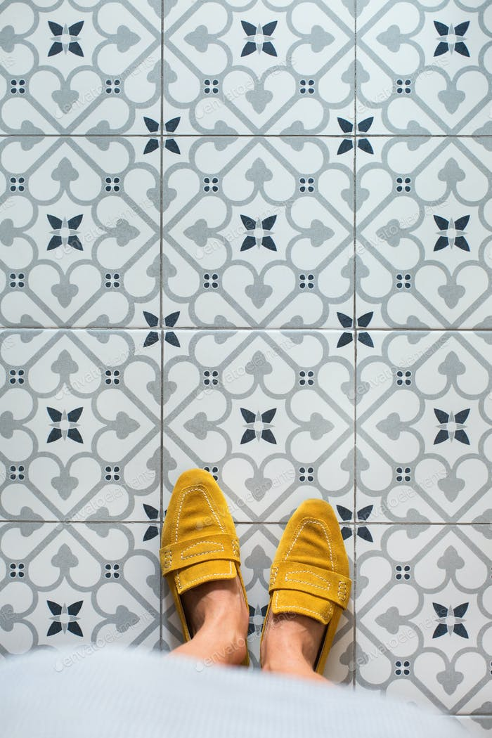 Selfie of female feet in yellow shoes on mosaic floor