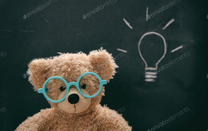 Cute teddy wearing glasses against blackboard with a lightbulb