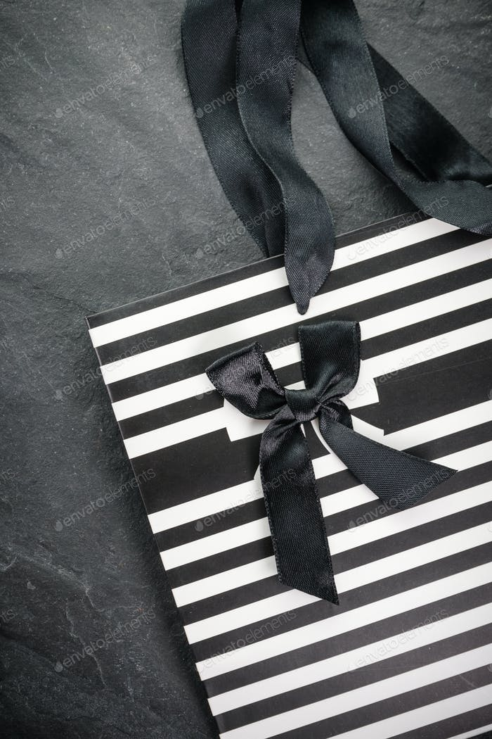 White packet in black stripes with handles ribbons and a black bow