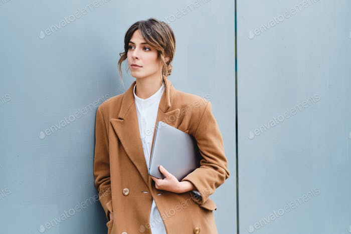 Young beautiful stylish businesswoman in coat with laptop intently looking away outdoor