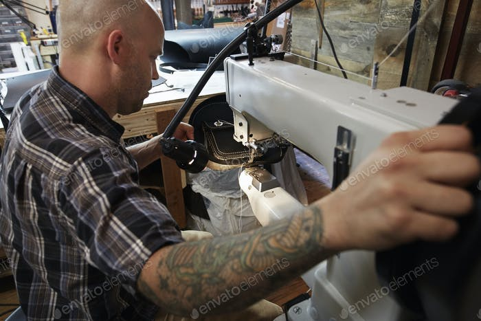 A leather worker, craftsman using an industrial sewing machine on leather material, making a bag.