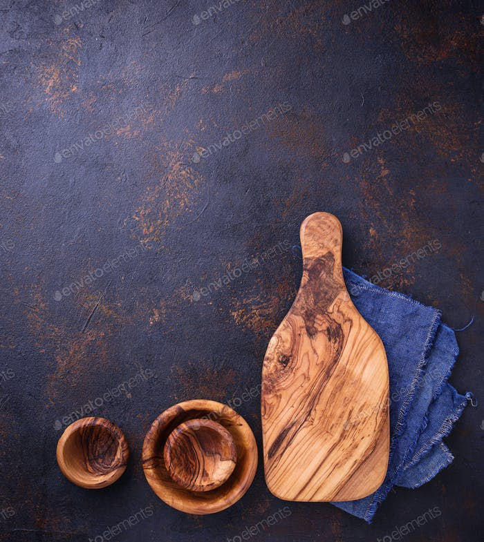 Empty wooden cutting board and bowls on rusty background