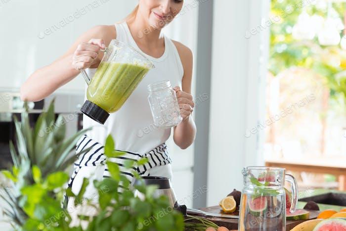 Glückliche Frau gießt grünen Cocktail