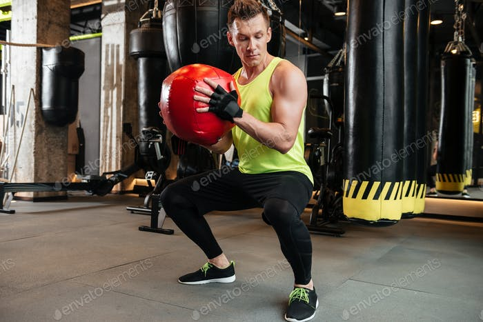 Strong fit sportsman doing squats with weight ball