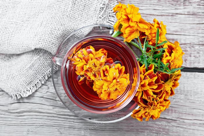 Tea herbal of marigolds in glass cup on board top