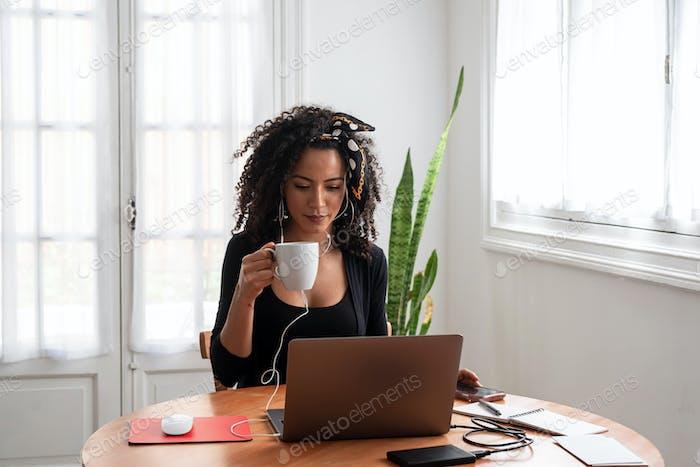 Lateinische Frau, die zu Hause mit Laptop und Dokumenten arbeitet