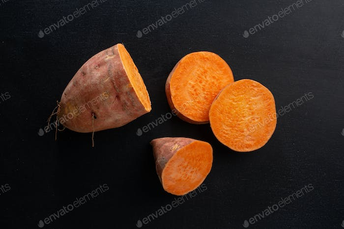 Raw sweet potato on dark background