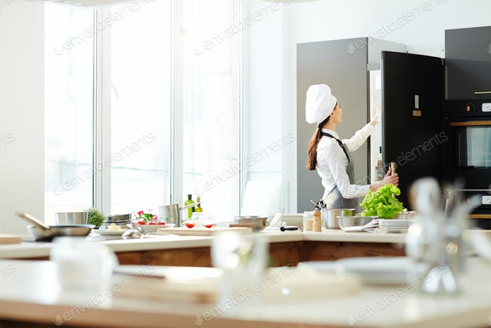 Female chef in hat opening refrigerator
