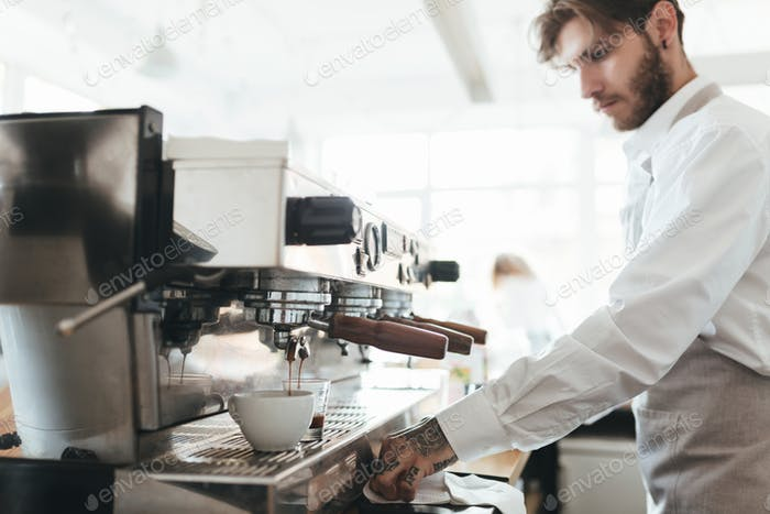 Young barista in apron and white shirt making coffee by coffee machine at counter in restaurant