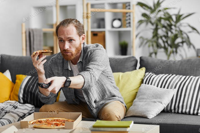 Single Man Eating Pizza while Watching TV