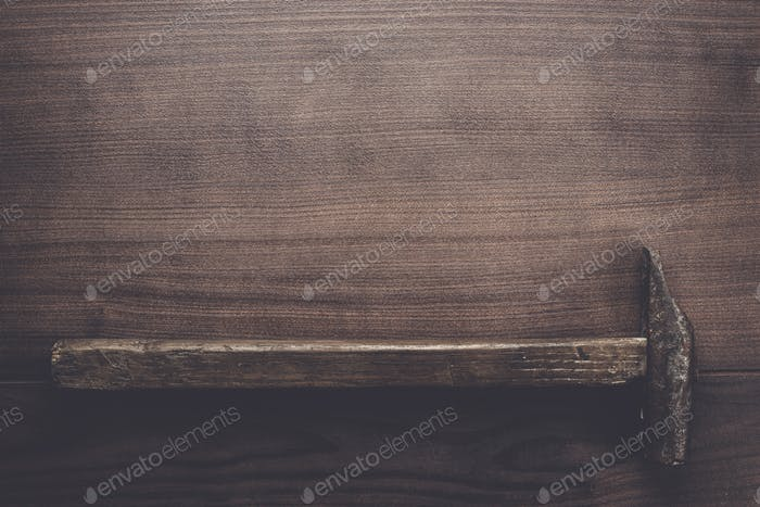 old rusty hammer on wooden background