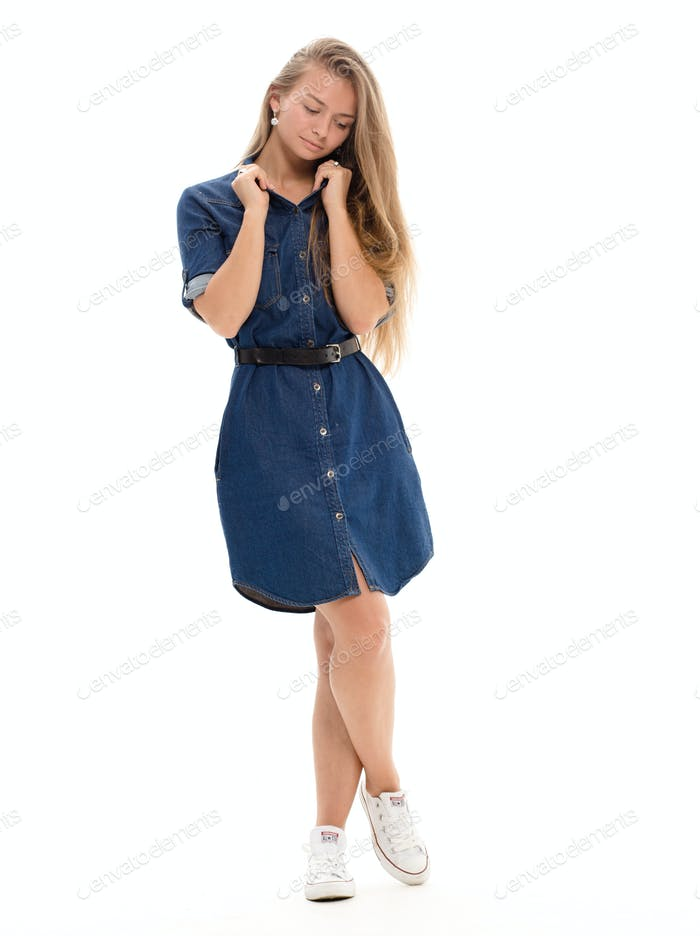 Young blond beautiful woman full length in jeans dress. Isolated on white