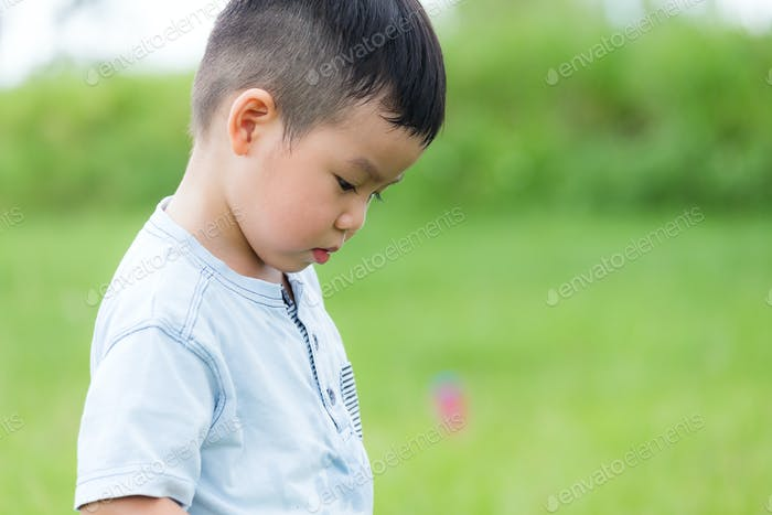 Little boy feeling unhappy and looking down