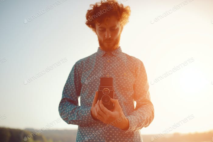 The red-haired guy holding a medium format film camera in his hands