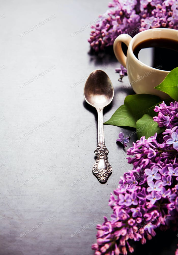 Black coffee in a cup, a spoon and fresh lilac flowers on black background
