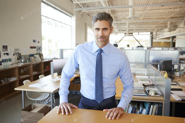 White male architect behind desk in office looking to camera
