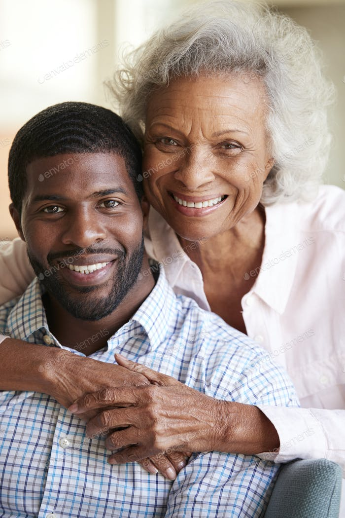 Portrait Of Smiling Senior Mother Hugging Adult Son At Home