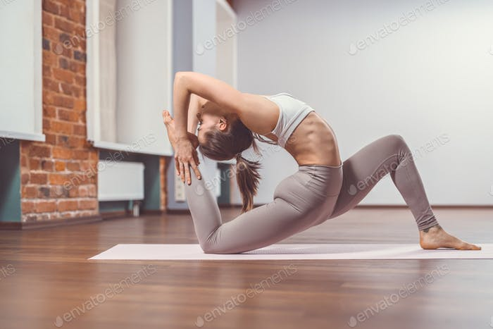 Young girl practicing yoga indoors