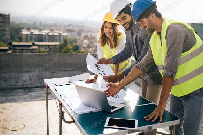 Architects team and engineers looking paper plans at construction site