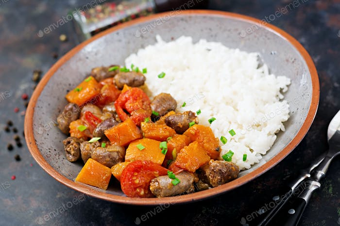 Chicken hearts with pumpkin and tomatoes in tomato sauce. The garnish is served with boiled rice.