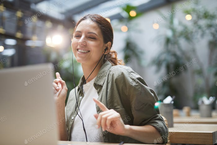 Young Woman Enjoying Work in Cafe