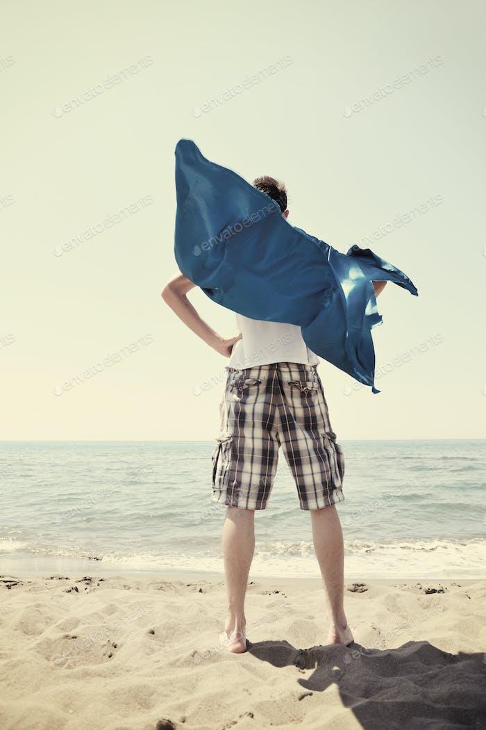 funny superhero standing on beach