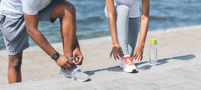 Afro Couple Lacing Shoes Next To River Embankment, Cropped