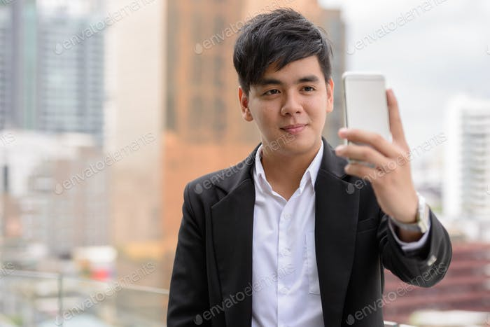 Portrait of young handsome Asian businessman taking selfie in the city