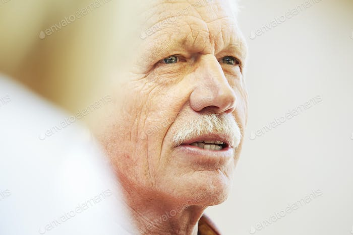 Portrait of a senior man with moustache sitting outdoors.