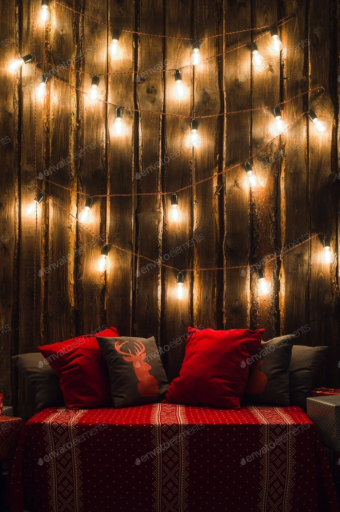 Christmas decorated place in a room with old wooden wall, lamps, red deer pillows and plaid