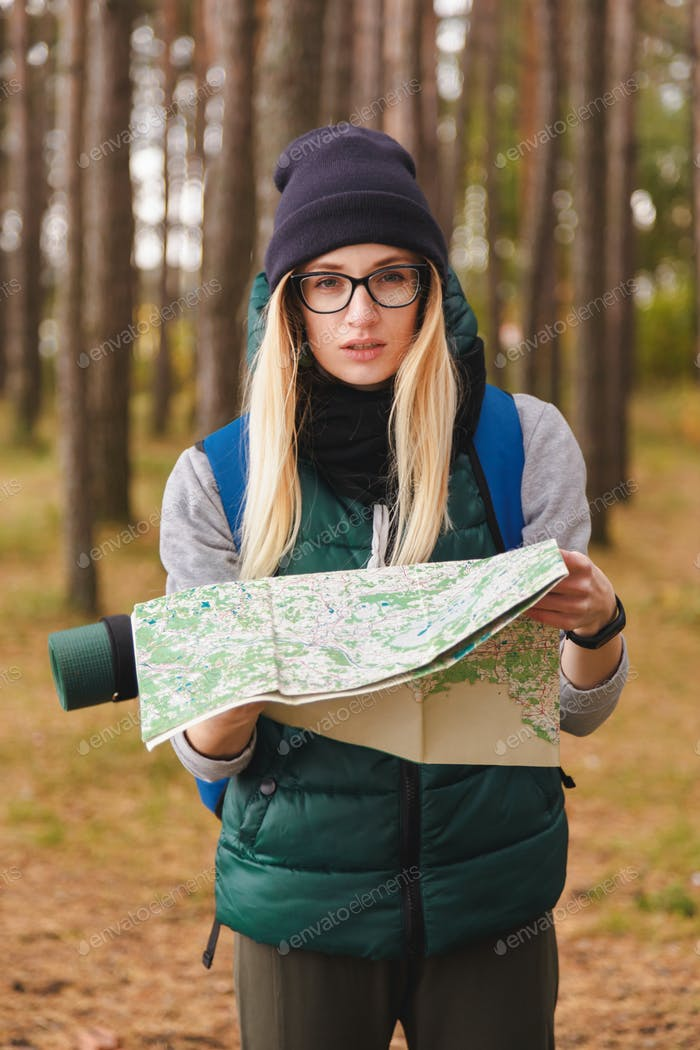 A beautiful young woman with travel map and backpack in pine plantations.